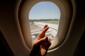 Male passenger crossing fingers while plane takes off